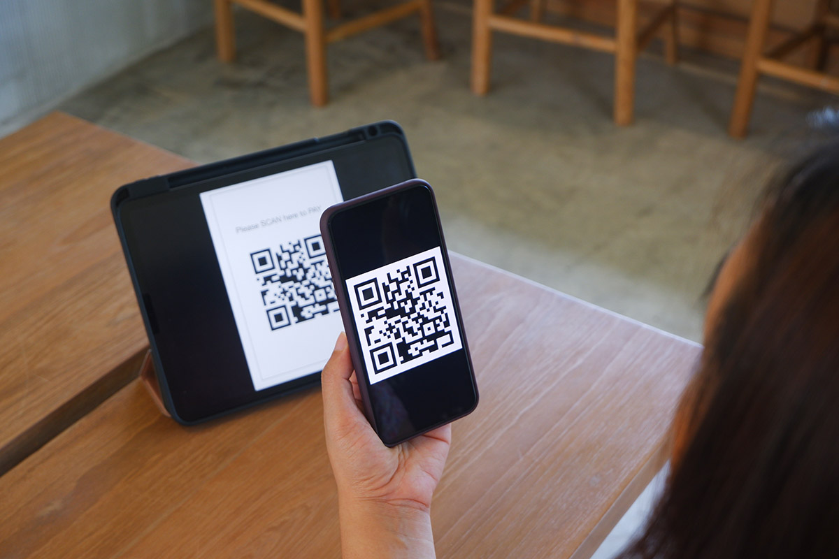 Women's hand uses a mobile phone application to scan QR codes in stores that accept digital payments without money and plastic tags on the table. QR code payment and cashless technology concept .